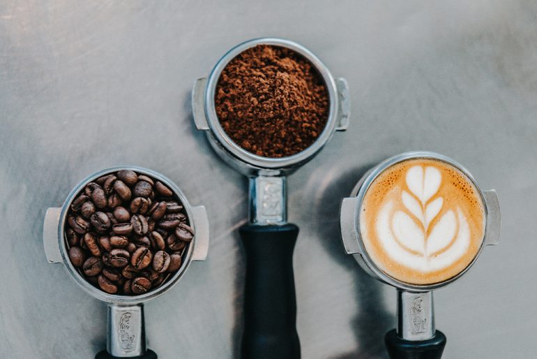 Three espresso portafilters lined up. One filled with beans, one filled with grounds, and the final one filled with a shot of espresso and milk designed to look like a tiny latte